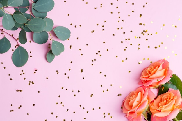Угловая декоративная рамка из розовых цветов, эвкалиптовых веточек и карнавальных декоративных ярких конфетти-звезд на светло-розовом фоне.