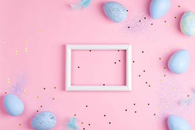 Corner frame from handmade painted eggs of pastel blue colors, photo frame and light feathers