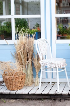 Corner of garden in fall. romantic porch, patio, chair and basket with spikelets near wooden blue house in countryside. terrace in rustic style. old coffee terrace, street cafe. modern interior design