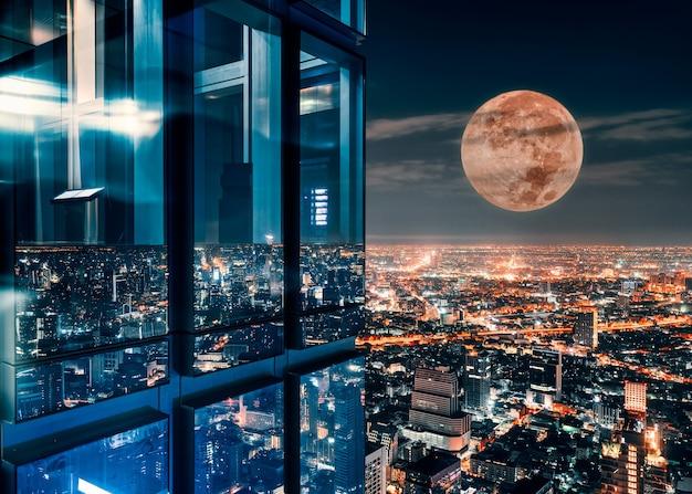 Corner glass window of skyscraper with supermoon glowing on illuminated city at bangkok