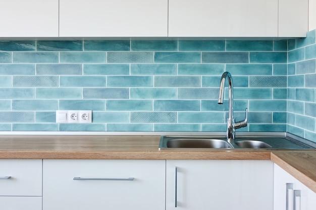 Угловая современная бело-синяя кухня, чистый дизайн интерьера с раковиной