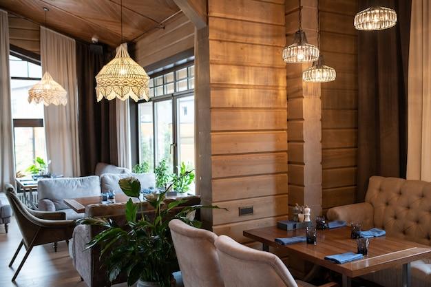 Уголок современного роскошного ресторана с деревянными столиками для гостей и мягкими креслами вокруг.