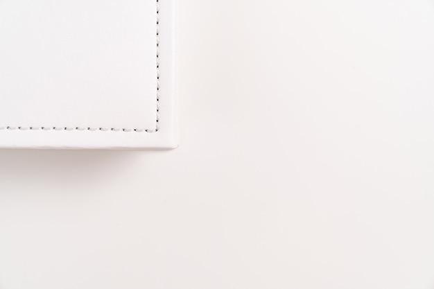 Уголок белой книги в кожаном переплете. полиграфическая продукция. фотоальбомы и альбомы. отдельные продукты.