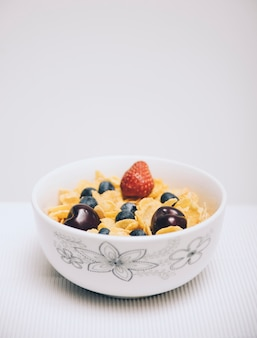 Cornflake cereals with berries in a bowl on white backdrop