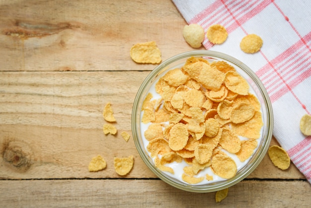 Cornflakes in bowl with milk on wooden background