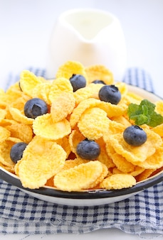 Cornflakes for breakfast with blueberries on a white background. selective focus.