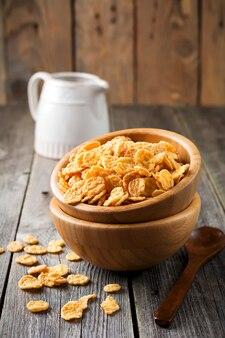 古い木の表面の竹皿で朝食用のコーンフレーク。セレクティブフォーカス。