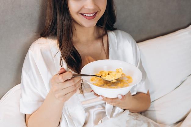 침대에서 아침 식사로 콘플레이크. 그녀는 침대에 누워 있는 동안 콘플레이크 접시를 들고 아름 다운 여자.