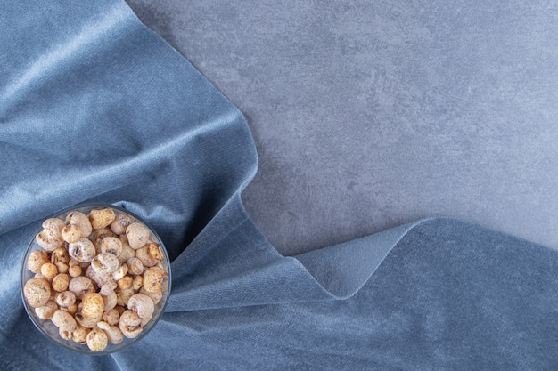 Cornflakes in a glass bowl on a piece of fabric , on the marble background.