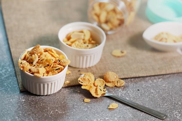 작은 흰색 그릇에 콘플레이크 곡물과 견과류는 신선한 음식을 위해 유제품 다이어트에 좋은 음식이며 매일 건강에 좋습니다.