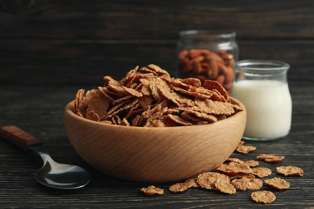 Cornflakes, milk, almond and spoon on wooden table