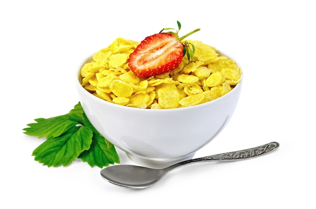 Cornflakes in a white bowl, berries and strawberry leaves, spoon isolated on white background