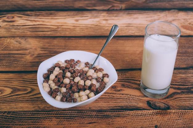 Кукурузные хлопья со стаканом молока на деревянном.