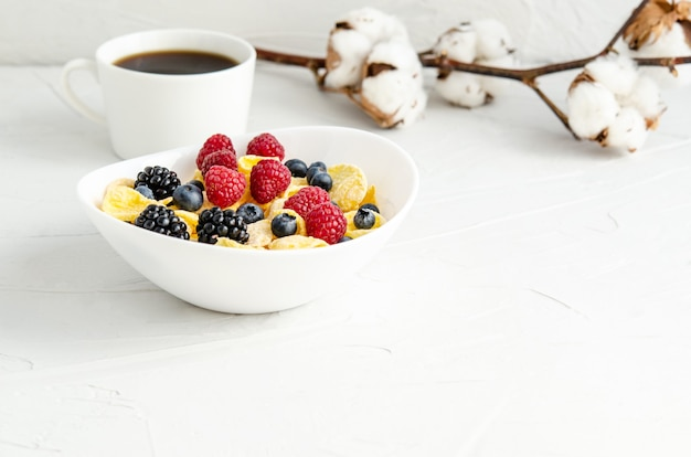 Cornflakes with fresh berries on a plate on a white surface