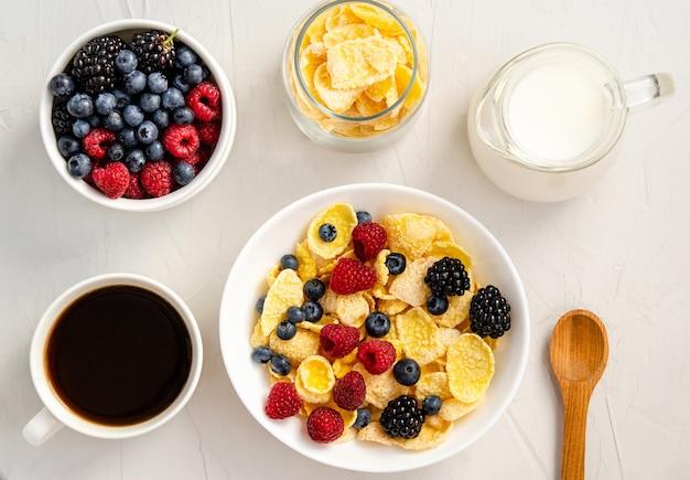 白い背景の上のミルクと新鮮なベリーとコーンフレーク。朝食や軽食のコンセプト。フラットレイ。上からの眺め。