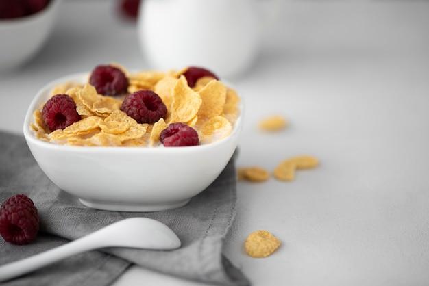 Кукурузные хлопья с молоком и малиной на белом столе