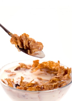 Cornflakes with milk in a bowl closeup isolated on white