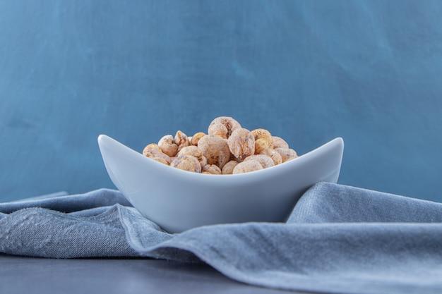 Cornflakes con muesli in una ciotola su un pezzo di tessuto, sullo sfondo di marmo. foto di alta qualità