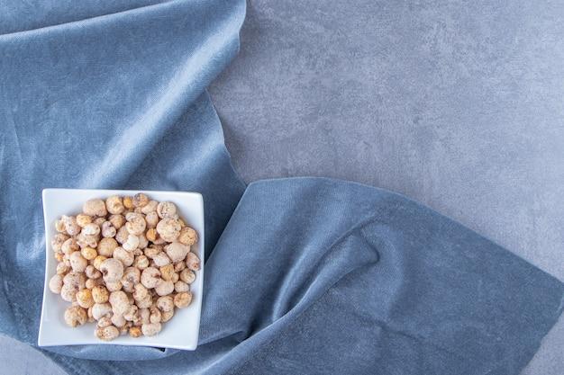 大理石のテーブルの上に、一枚の布の上にボウルにミューズリーが入ったコーンフレーク。