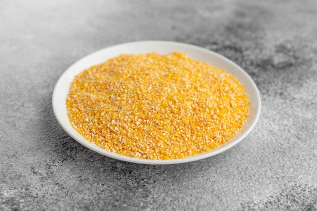 Cornmeal mush in a white saucer on a gray concrete background