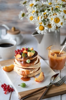 Cornmeal pancakes with salted caramel served with berries and fruits on a white wooden background.