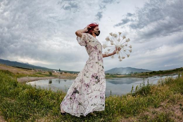 코로나 패션. 장식용 코로나 공을 들고 호수 옆에 걷는 빨간 머리 소녀의 극적인 샷