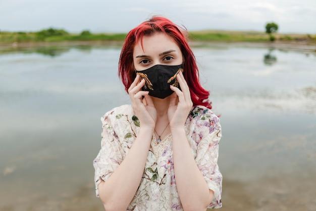 코로나 패션. 창조적 인 의료 마스크를 착용하고 두 손으로 잡고 빨간 머리 소녀
