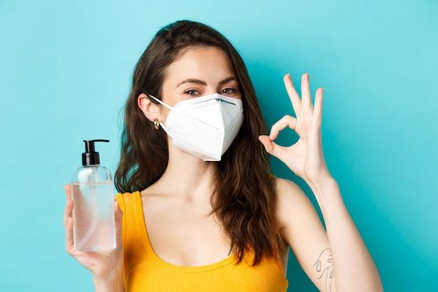 Концепция пандемии и здравоохранения короны улыбающаяся красивая девушка в респираторе показывает дезинфицирующее средство для рук б ...