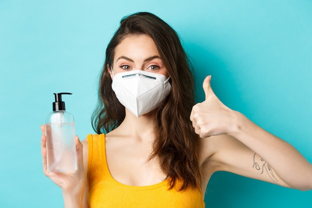 Corona pandemic and healthcare concept close up of young attractive woman recommending you hand sani...