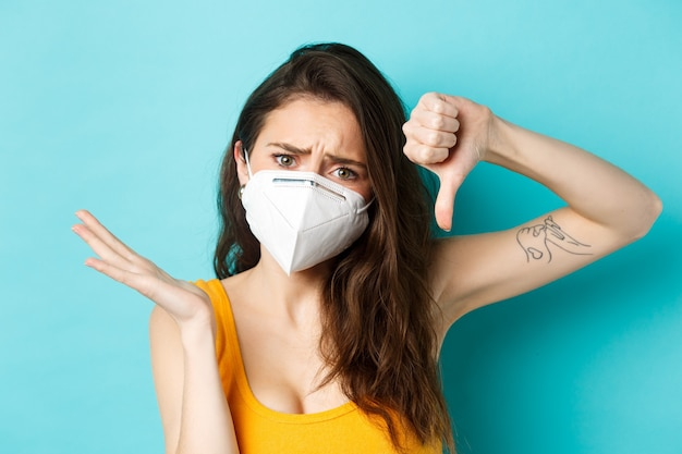 Corona pandemic and healthcare concept frustrated young woman showing thumb down and look confused d...