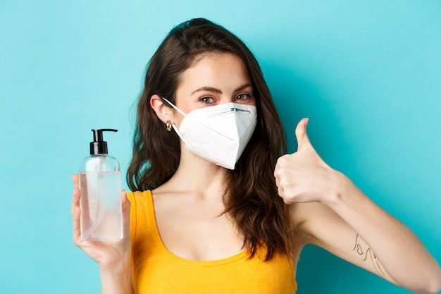 Corona pandemic and healthcare concept smiling beautiful girl in respirator showing hand sanitizer b...