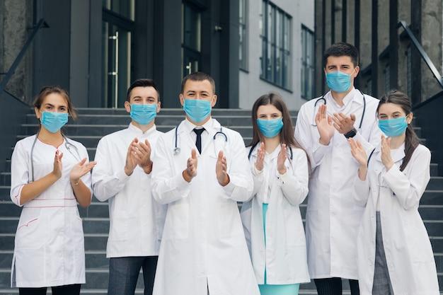 Корона вирус и концепция здравоохранения. медицинский персонал больницы, который борется с коронавирусом, аплодирует людям за их поддержку. группа врачей с масками, глядя на камеру.