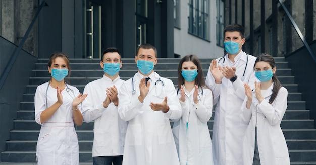 コロナウイルスとヘルスケアの概念。コロナウイルスと戦っている病院の医療スタッフは彼らのサポートを人々に拍手を送ります。カメラ目線のフェイスマスクを持つ医師のグループ。