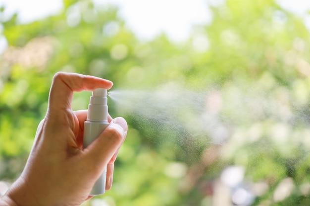 コロナウイルス(covid-19)と生殖保護の概念。アルコール70%スプレーのミニボトルを押しながらスプレーする人間の手のクローズアップ。