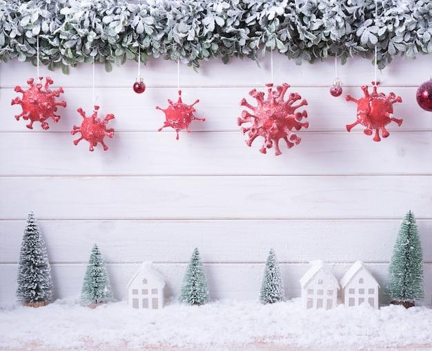 Вирус короны (covid-19), созданный путем лепки из глины, нарисованной среди рождественских и новогодних украшений для празднования на белом деревянном фоне с копией пространства.