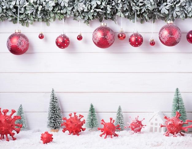 Вирус короны (covid-19), созданный путем лепки из глины, нарисованной среди украшений с рождеством и новым годом для празднования на белом деревянном фоне с копией пространства.