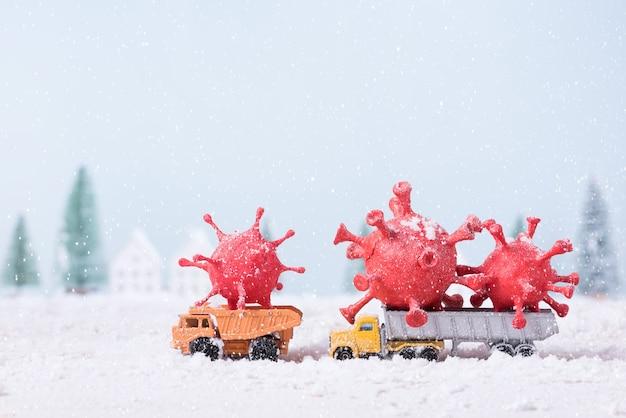 장난감 자동차 트럭에 그려진 점토를 성형하여 만든 코로나 바이러스 (covid-19)는 자연 경관 배경의 크리스마스 트리 현장에서 눈을 뛰고 있었다.