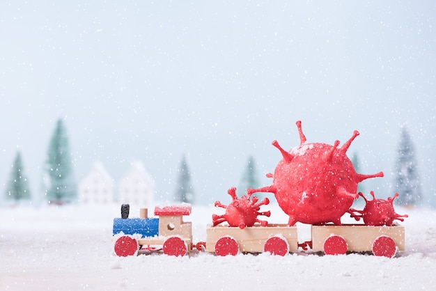 장난감 기차에 그려진 점토를 성형하여 만든 코로나 바이러스 (covid-19)는 자연 경관 배경의 크리스마스 트리 현장에서 눈을 뛰고 있었다.