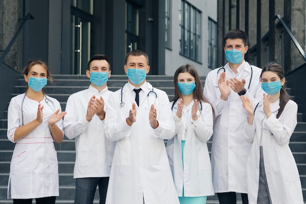 Corona virus and healthcare concept. medical staff from the hospital who are fighting coronavirus applaud back the people for their support. group of doctors with face masks looking at camera.