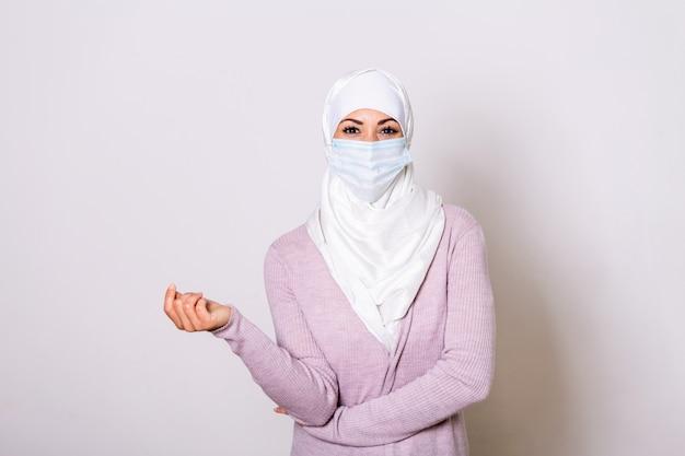 コロナウイルスパンデミック。ウイルスから彼女を保護するための医療マスクとヒジャーブの女性。