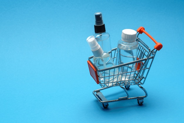 Corona virus protection hygiene concept - alcohol hand sanitizer liquid in shopping cart troplley on blue background. . hand wash in the basket