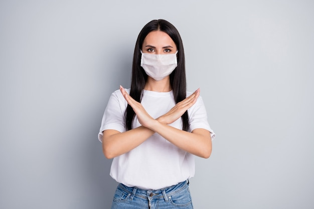 コロナウイルスは汚染を止めます。自信を持って厳格な女の子が手を組んで歩くことを禁じますエアウェアホワイトメディカルマスクtシャツデニムジーンズ灰色の背景の上に分離