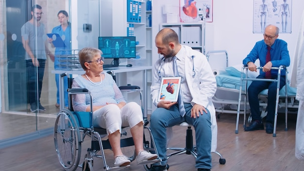 Coronary artery disease explanation from doctor to senior handicapped retired woman in wheelchair in a recovery clinic. elderly patients with walking frame, disabled disability in hospital, medical ad