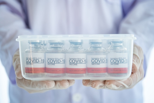 Coronavirus - 2019-ncov or covid-19 vaccine bottles for injection use only. doctor picking up bottle of coronavirus vaccine from plastic carton . covid-19 vaccine close up with copyspace.