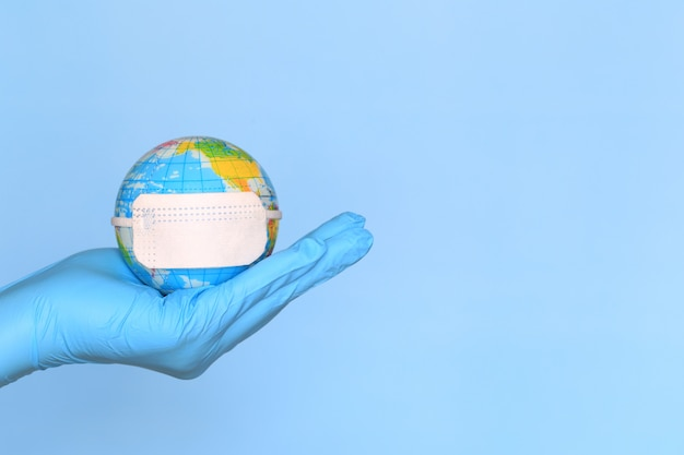 Coronavirus 2019-ncov, doctor hand holding world or earth with wearing protective medical mask on blue background, healthcare and safety concept