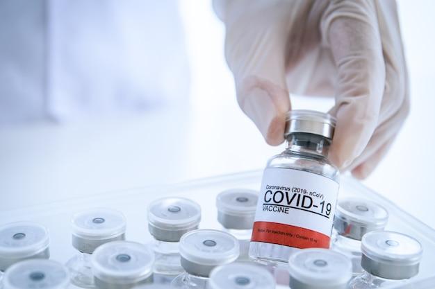 コロナウイルス-2019-注射用のみのncovまたはcovid-19ワクチンボトル。プラスチックカートンからコロナウイルスワクチンのボトルを拾う医師。 covid-19ワクチンはコピースペースでクローズアップします。