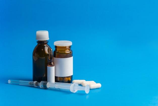 Вспышка коронавируса 2019-ncov. таблетки и шприц на синем фоне. таблетки и лекарства, уход во время болезни.