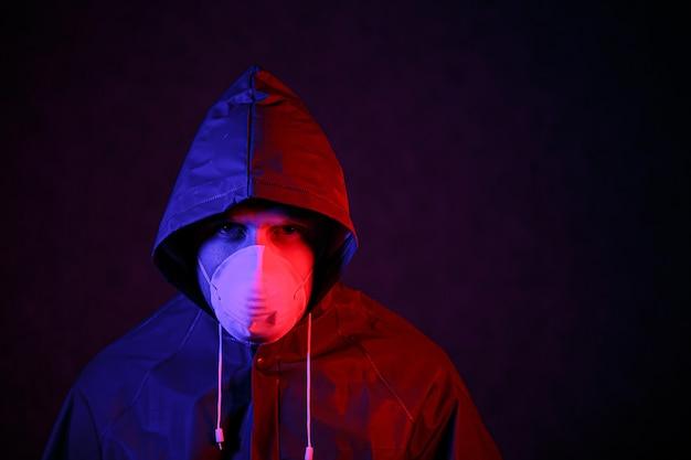 코로나 바이러스. 빨간색과 파란색 빛의 마스크와 화학 보호복을 입은 남자. 바이러스와 싸워라