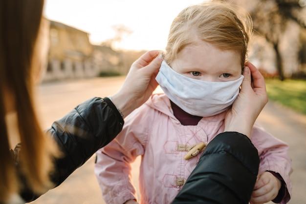 コロナウイルスと大気汚染の概念。小さな女の子とマスクを身に着けている母親が通りを歩きます。ママはマスクの子を修正します。パンデミックウイルスの症状。屋外の子供と家族。病気からの保護。