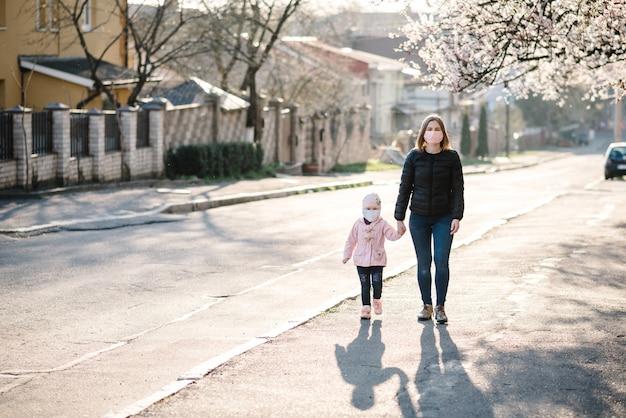 코로나 바이러스 및 대기 오염 개념. 어린 소녀와 어머니 마스크를 쓰고 거리에 걸어. 유행성 바이러스 증상. 나무 꽃의 배경에 대해 야외에서 아이와 가족. 질병 보호